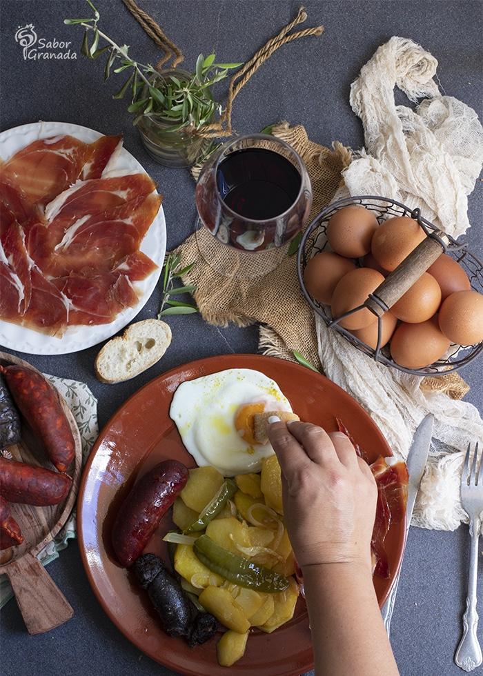 Mojando huevo en el plato Alpujarreño - Sabor Granada