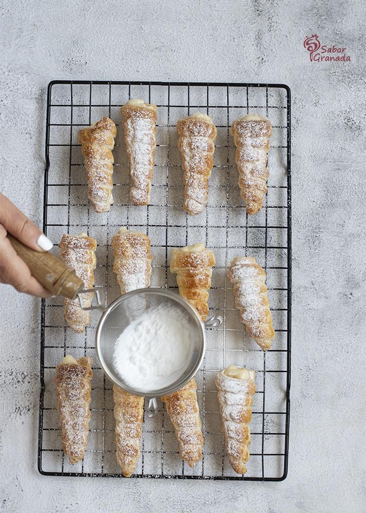 Tercer paso para hacer canutillos rellenos de crema pastelera: se espolvorean con azúcar glass - Sabor Granada