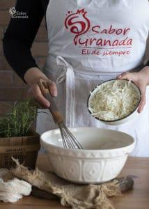 Cuarto paso de la receta de magdalenas de queso y romero: añadimos el queso - Sabor Granada