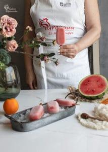 Uno de los polos de sandía y naranja en la mano - Sabor Granada